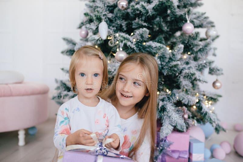 Två systrar hemma med julgranen och gåvor Lyckliga barnflickor med julgåvaaskar och garneringar royaltyfria bilder