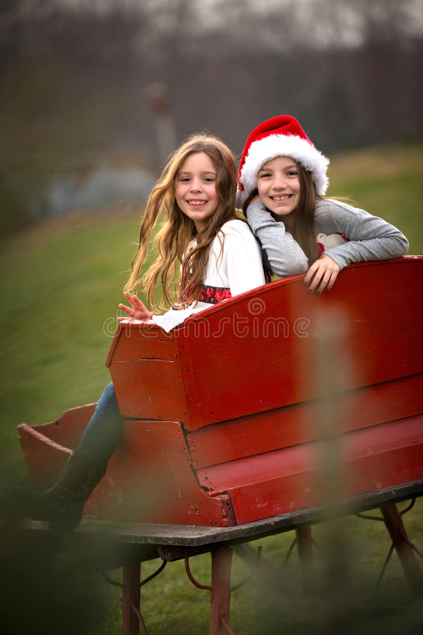 Två systrar i röd släde royaltyfri fotografi