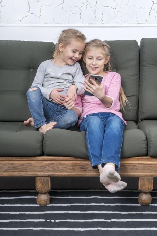 Två systrar med smartphonen på soffan royaltyfria bilder
