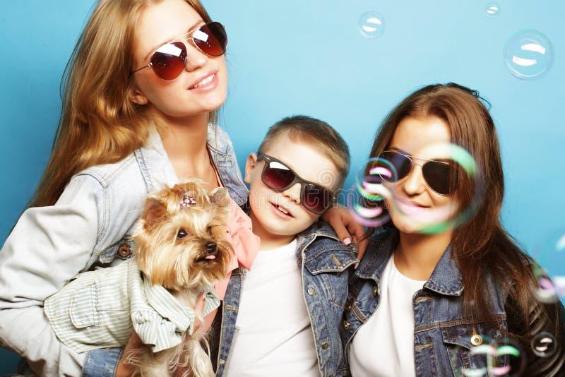 Två systrar och broder med den yorkshire terriern royaltyfri bild