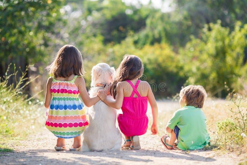 Två systrar och en yngre bror som går hunden royaltyfria foton
