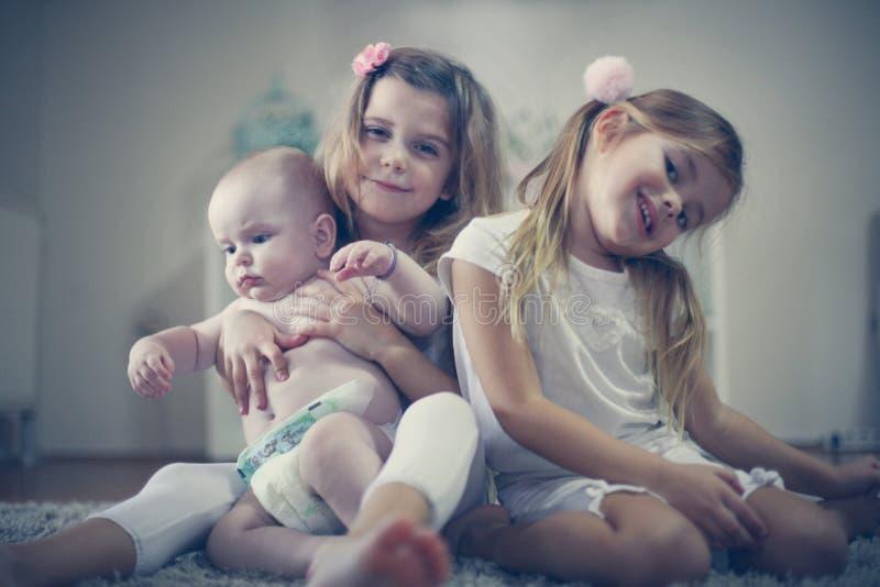 Två systrar poserar till kameran med behandla som ett barn brodern royaltyfria bilder