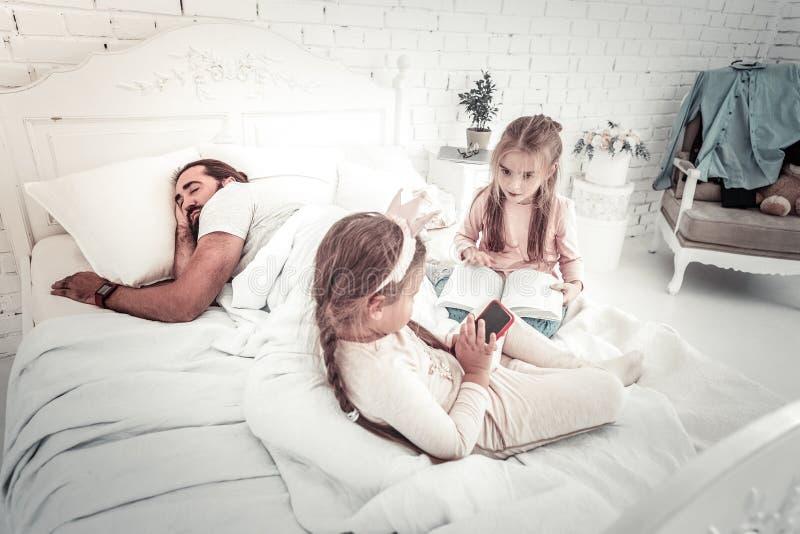 Två systrar som har gyckel på sängen, medan deras fader sover arkivbilder