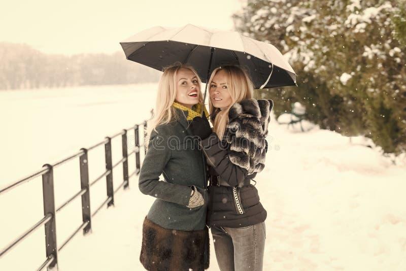 Två systrar som ler under paraplyet på vinterdag royaltyfri bild