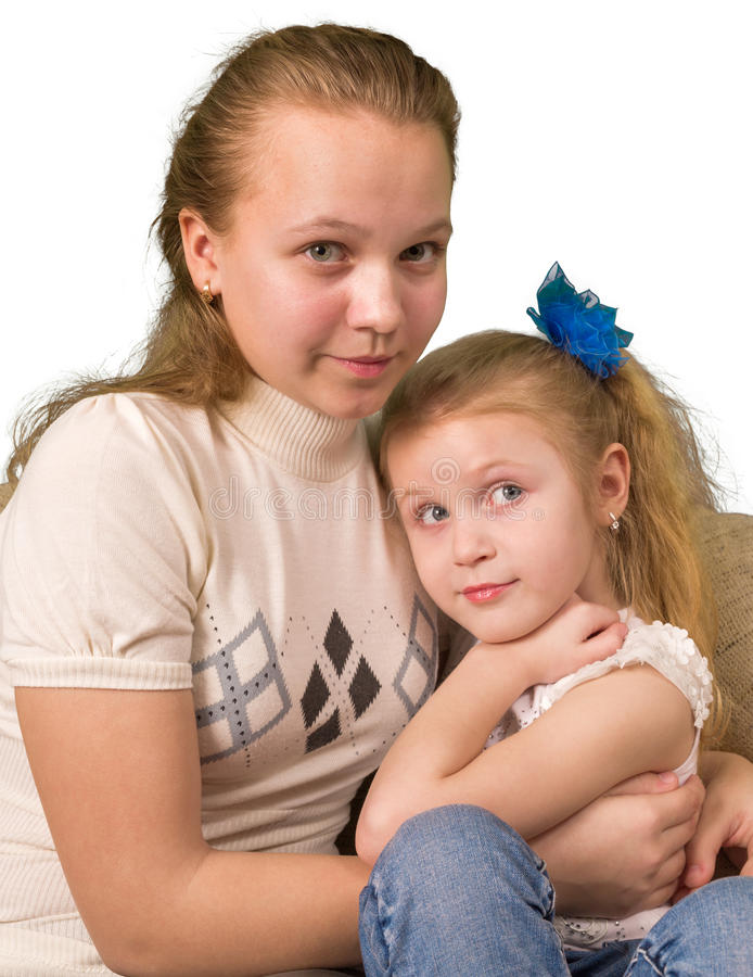 Två systrar som sitter tillsammans isolerat på vit royaltyfri foto
