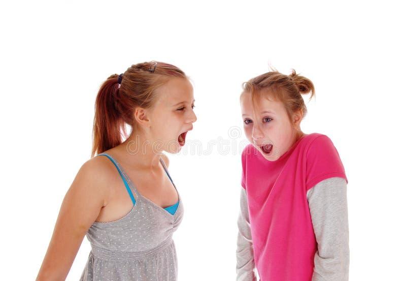 Två systrar som skriker på de royaltyfria foton