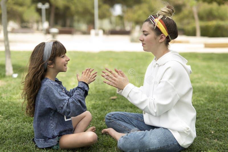 Två systrar som spelar i ett parkerasammanträde på gräset royaltyfri bild