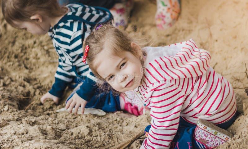 Två systrar som spelar på sanden i skogen royaltyfri fotografi