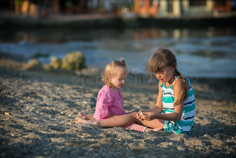 Två systrar som spelar på stranden arkivbild