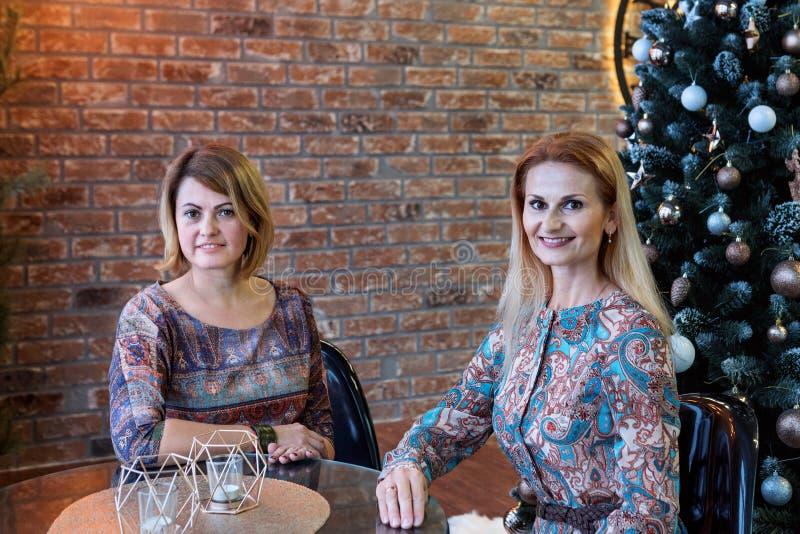 Två systrar unga kvinnor sitter vid ett bord i ett kafé som är dekorerat med en julgran royaltyfria foton