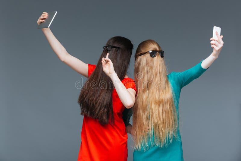 Två täckte kvinnor vänder mot med långt hår och taselfie arkivbilder