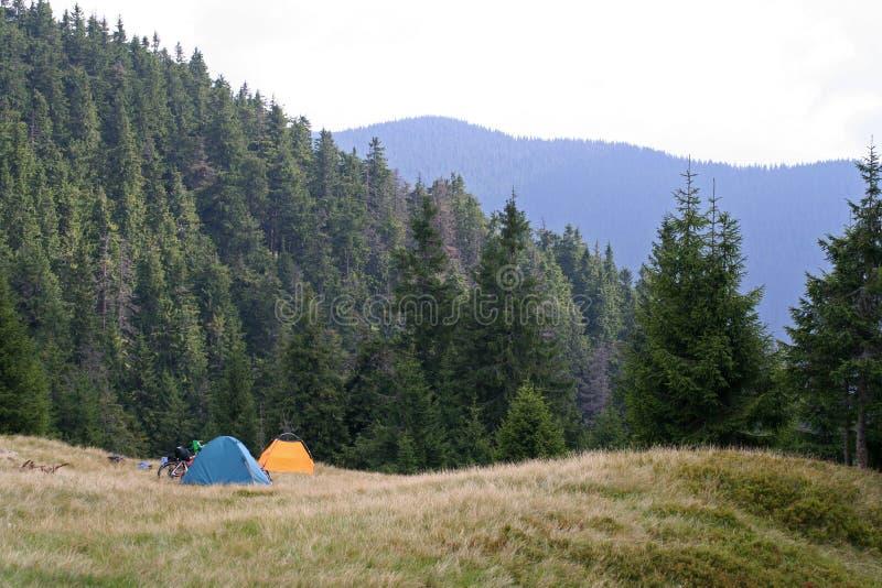Två tält och cyklar på en äng i bergen royaltyfria bilder