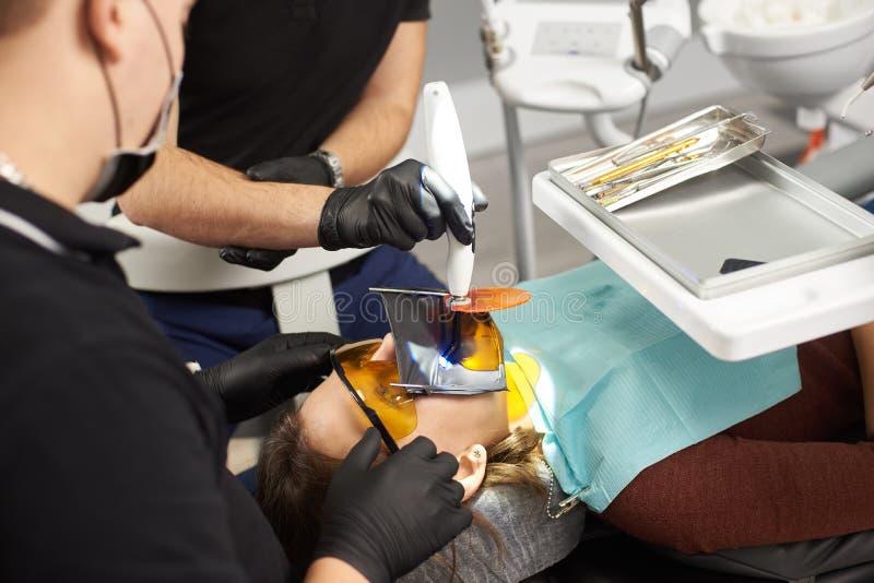 Två tandläkare i svarta dräkter som fixar tänderna av en patient med en kofferdam på framsidan royaltyfri fotografi