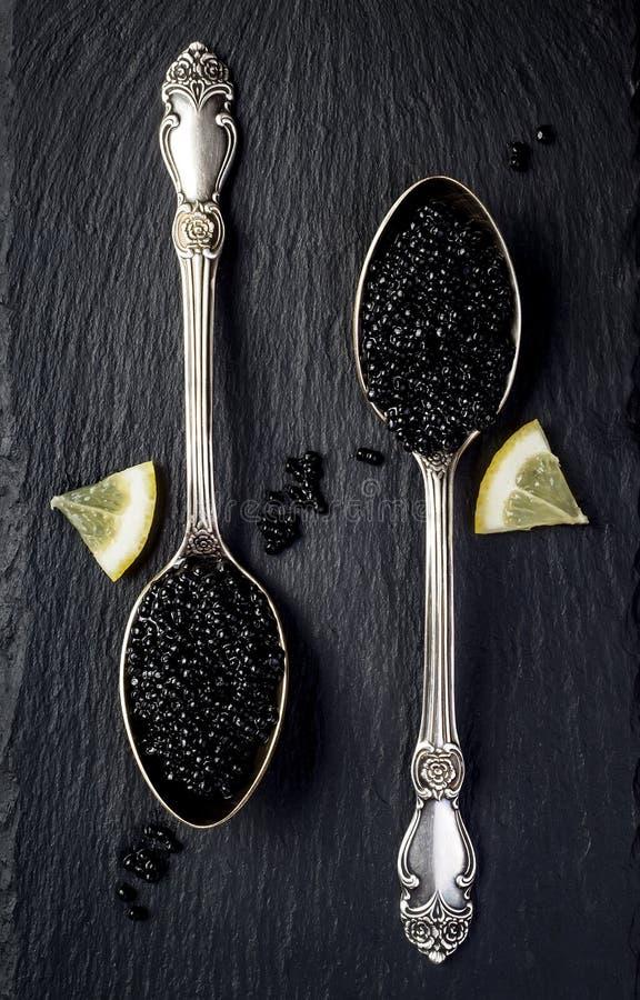 Två tappningsilverskedar med den svarta störkaviaren på svart kritiserar stenbakgrund Bästa sikt, lekmanna- lägenhet royaltyfri foto