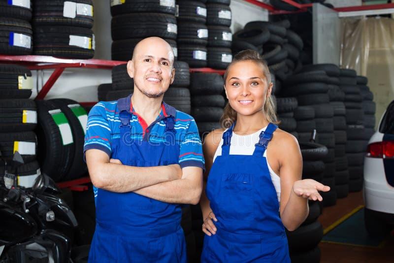 Två tekniker i overaller som står på tjänste- punkt för bil royaltyfri foto