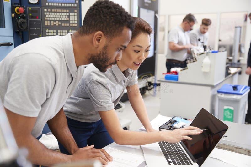 Två teknikerer som använder CAD som programmerar programvara på bärbara datorn royaltyfri bild