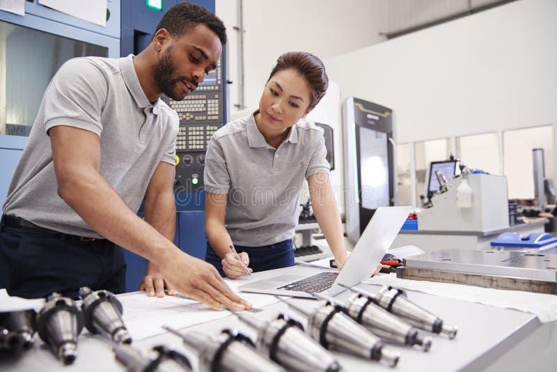 Två teknikerer som använder CAD som programmerar programvara på bärbara datorn royaltyfria bilder