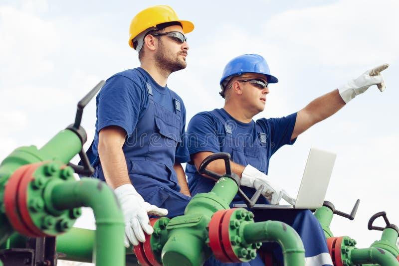 Två teknikerer som arbetar inom fossila bränslenraffinaderi royaltyfria bilder