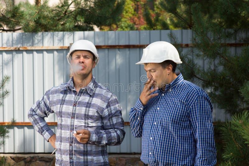 Två teknikerer som tar ett rökavbrott fotografering för bildbyråer