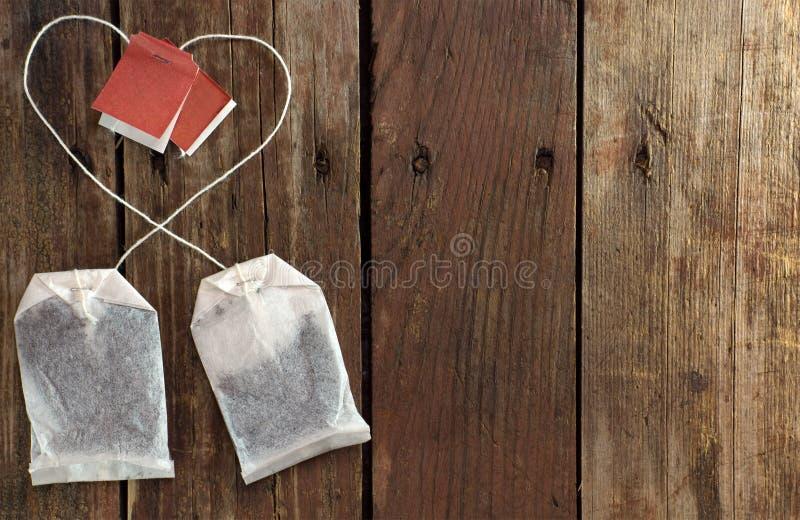 Två tepåsar med trådar som läggas ut i en hjärtaform royaltyfria foton