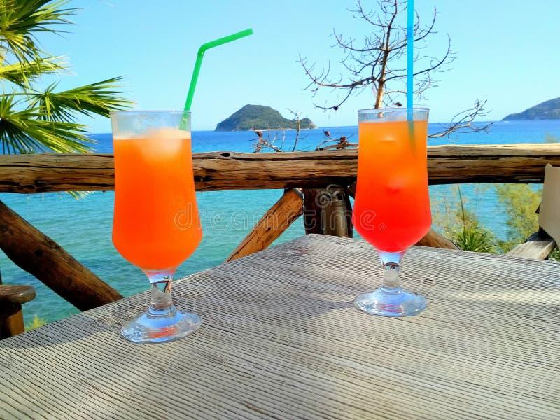Två tequilasoluppgångcoctailar som förbiser ön och havet royaltyfri bild