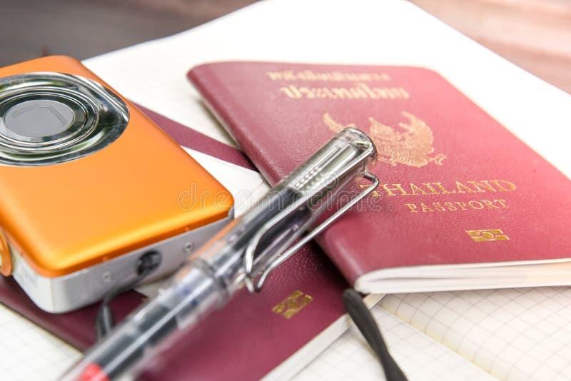 Två Thailand pass med den digitala kameran och boken som kontrollerar lis arkivbilder