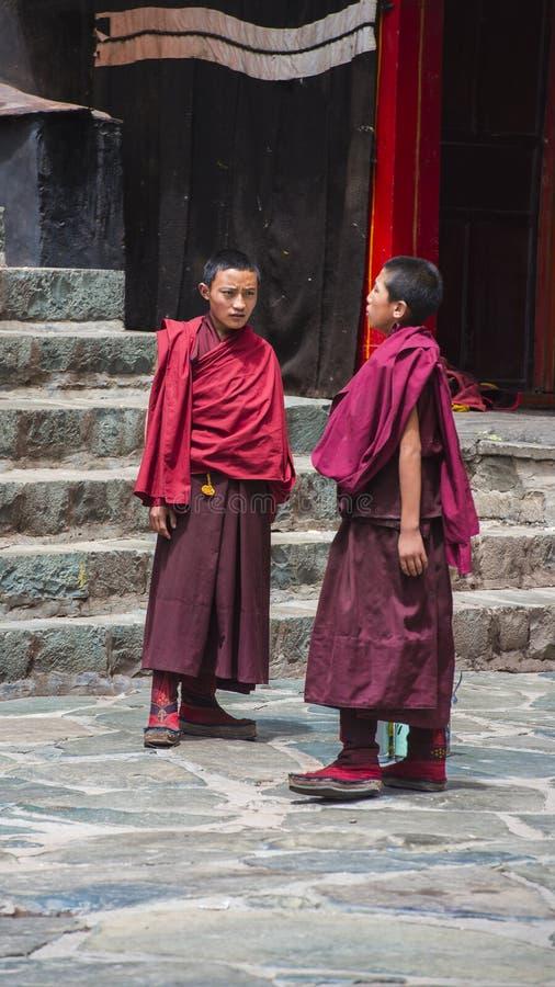 Två tibetana buddistiska munkar står i borggård av den Tashilhunpo kloster Shigatse Tibet fotografering för bildbyråer