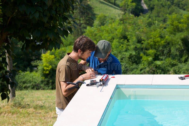 Två tilers som arbetar runt om simbassäng arkivbilder