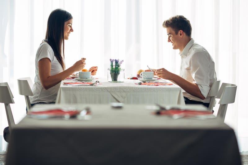 Två tillfälliga unga vuxna människor som har en konversation över ett mål Formellt förslag som talar i en restaurang Försökande m arkivbilder