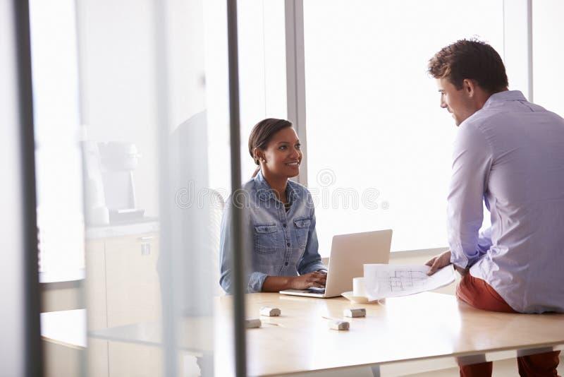 Två tillfälligt klädde Businesspeople som i regeringsställning arbetar arkivfoton