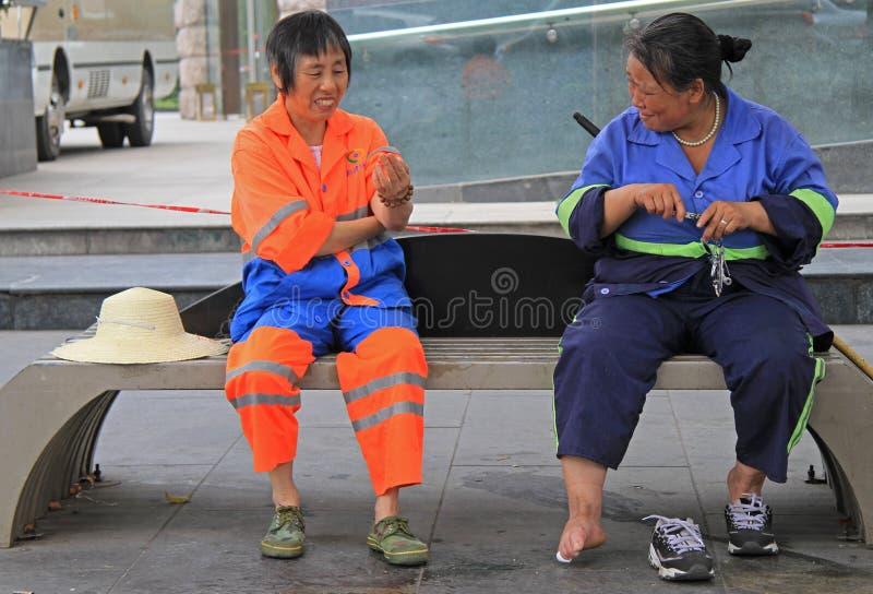 Två tjänste- arbetare vilar på en bänk som är utomhus- i Chengdu royaltyfri bild
