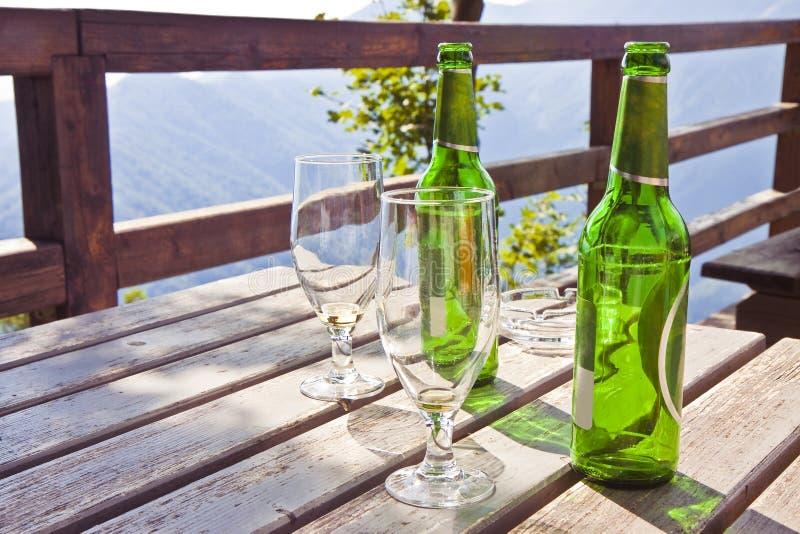 Två tomma ölflaskor med exponeringsglas på en trätabell - avbilda wi arkivbilder
