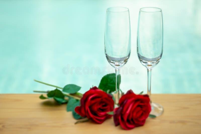 Två tomma champagneexponeringsglas med den nästa simbassängen för rosa blomma fotografering för bildbyråer