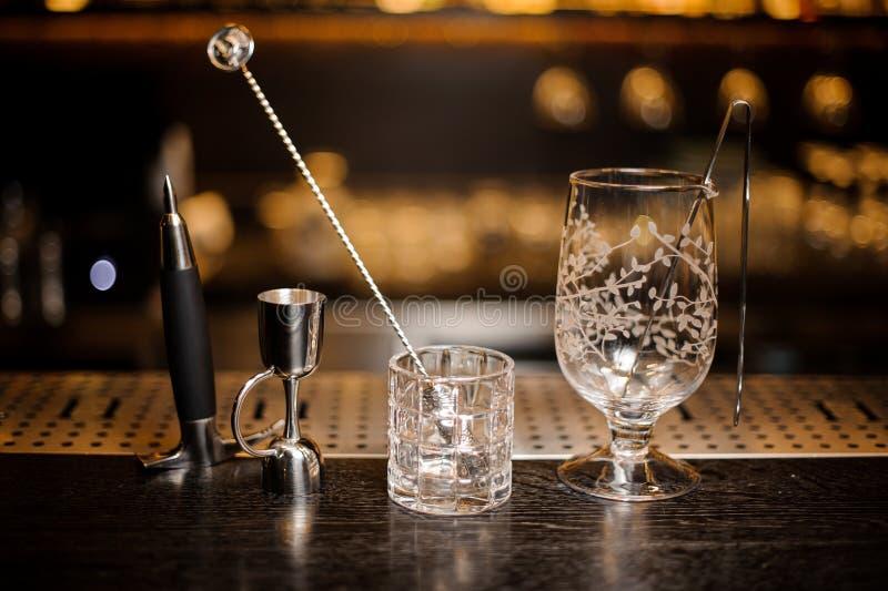 Två tomma coctailexponeringsglas som är ordnade på stången, kontrar royaltyfri bild