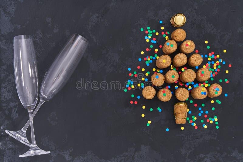 Två tomma exponeringsglas och julgran gjorde från använda champagneflaskkorkar med färgrika konfettier på svart bakgrund med kopi arkivbild