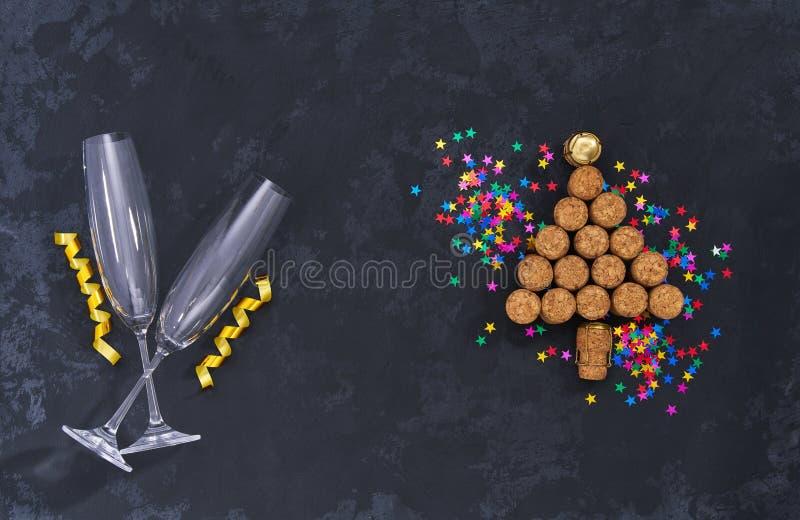 Två tomma exponeringsglas och julgran gjorde från använda champagneflaskkorkar med färgrika konfettier på svart bakgrund med kopi royaltyfri bild