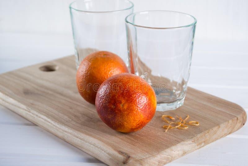 Två tomma exponeringsglas och Sicilian apelsiner royaltyfri bild