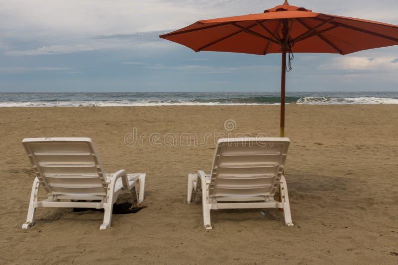 Tv? tomma plast- vita stolar under ett orange strandparaply p? en ?de strand i Costa Rica royaltyfri foto