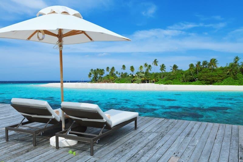 Två tomma sunbed på vattenvillan, Maldiverna ö royaltyfria foton