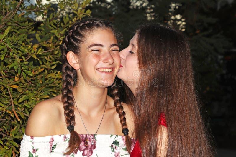 Två tonåriga flickor är att skratta som är lyckligt fotografering för bildbyråer