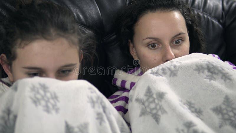 Två tonåriga flickor i pijamas som sitter på soffan med filten royaltyfria bilder