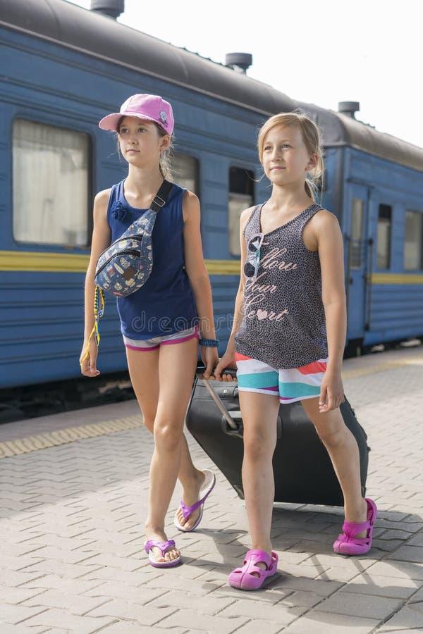 Två tonåriga flickor på drevstationen med en resväska Två systrar drar en stor och tung svart resväska mot arkivbilder
