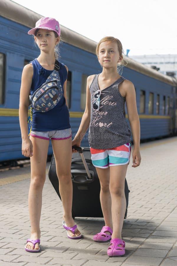 Två tonåriga flickor på drevstationen med en resväska Två systrar drar en stor och tung svart resväska mot royaltyfri bild