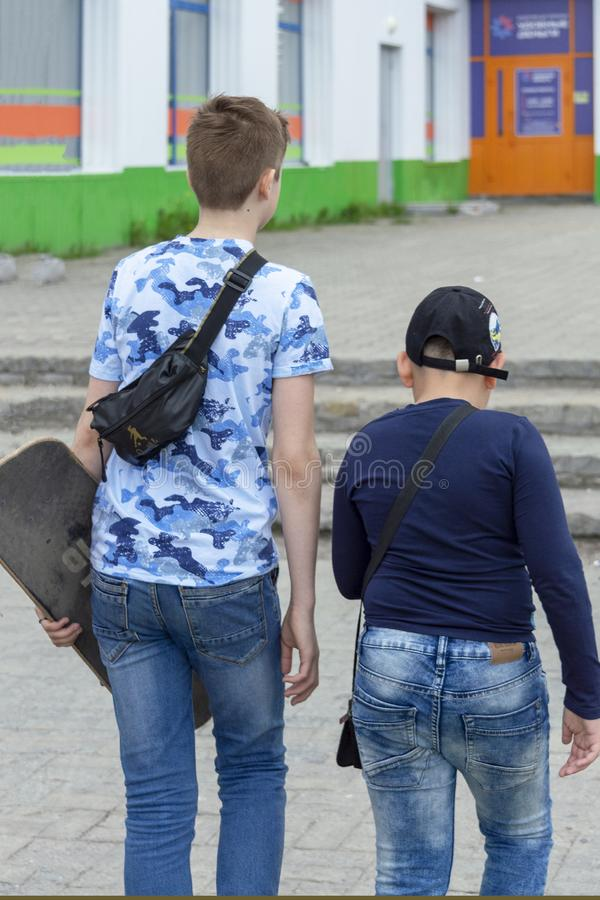 Två tonåriga grabbar går ner gatan i staden arkivfoto
