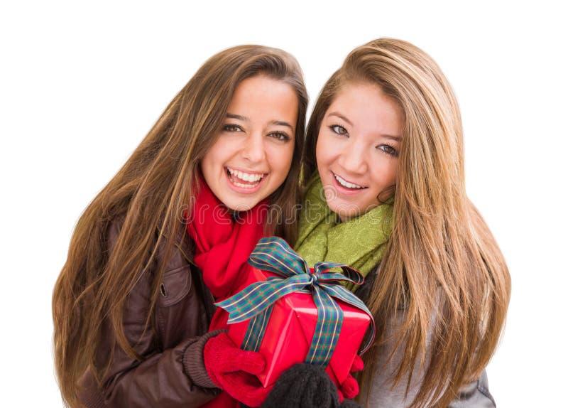 Två tonåriga kvinnlig för blandat lopp som rymmer en julgåva isolerad royaltyfria bilder