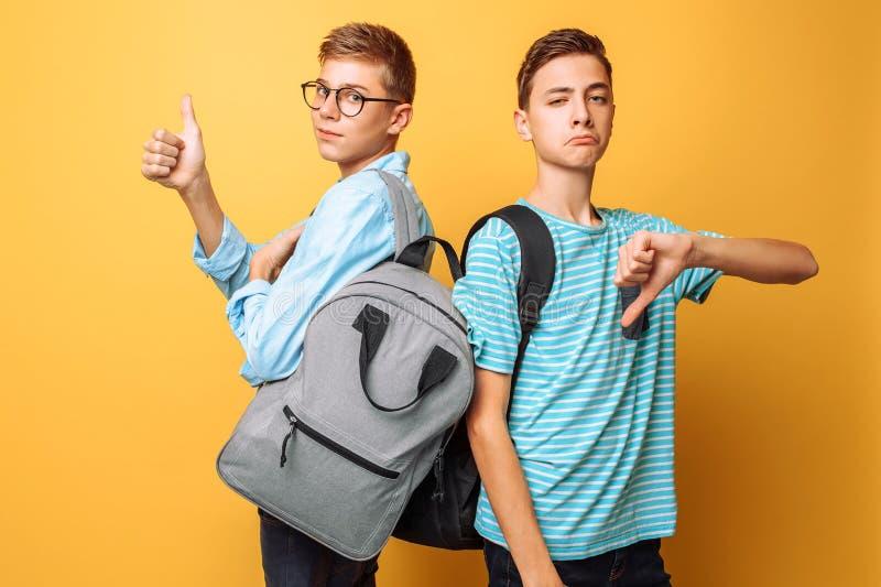 Två tonåringar, grabbar visar motsatta sinnesrörelser, vänner visar positiva och negativa gester, på en gul bakgrund royaltyfri fotografi
