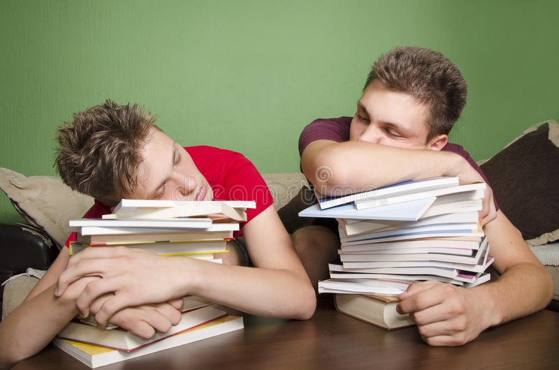 Två tonåringar som sover på böcker arkivbild