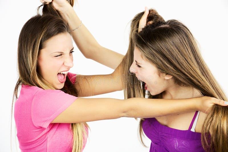 Två tonåringvänner som slåss dra isolerat långt hår royaltyfria bilder