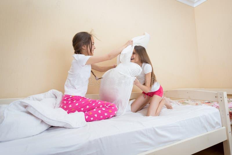Två tonårs- flickor i pyjamas som har gyckel och slåss med kudden royaltyfri bild