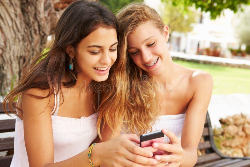 Två tonårs- flickor som använder mobiltelefonsammanträde parkerar på, bänken fotografering för bildbyråer